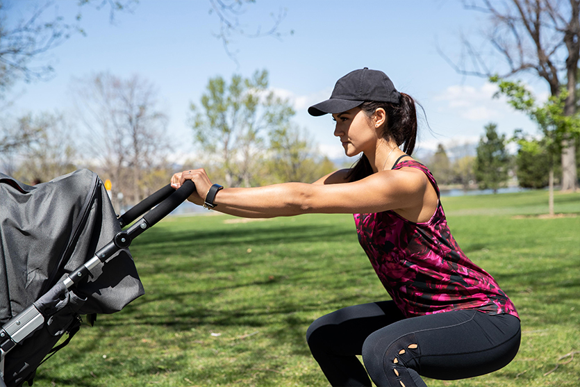 mom doing squats with a jogging stroller in a park