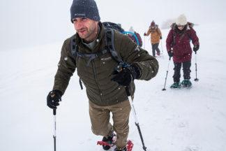 Group Of People Walking Through Snow In Snoeshoes