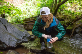 Girl Filling Up Water Bottle At Stream