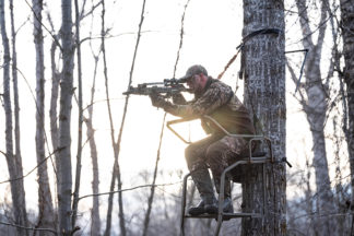 guy in the woods in a treestand