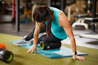 Woman Using Foam Roller In Gym