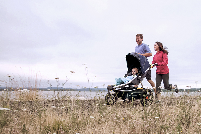 mom and dad running with their baby in a jogging stroller