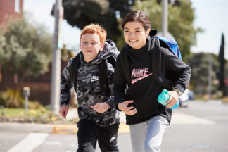two young kids wearing backpacks running for the school bus