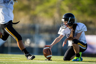 female football player holding the football for a field goal attempt