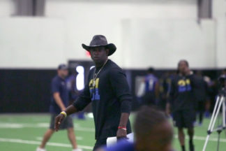 Deion Sanders Coaching Football Players On Indoor Football Field