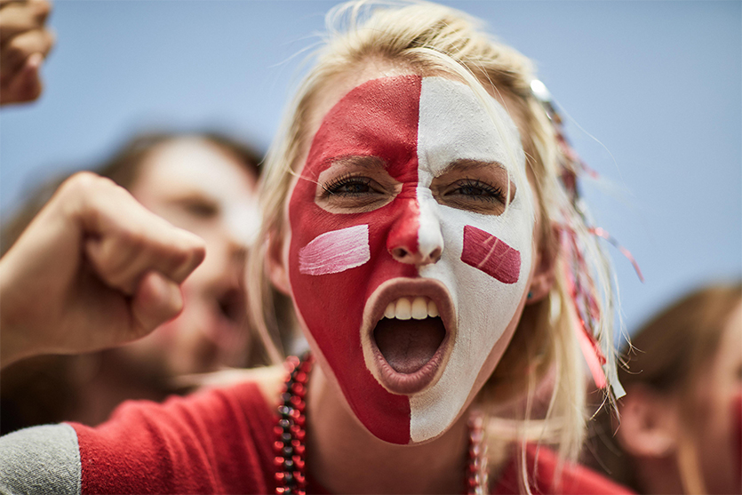 blonde woman with red and white facepaint cheering on her team at a game