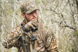 man in woods wearing camo with a hunting rangefinder