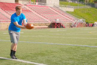 Football Player Punting A Football