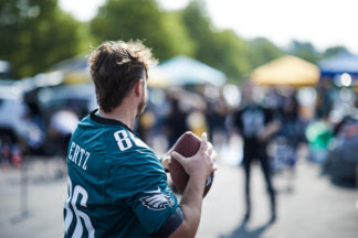 man at tailgate wearing Ertz Philadelphia Eagles jersey playing catch with a football