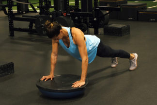 Woman Doing Push-Up On Balance Trainer