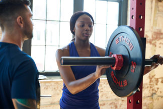 Woman Putting Clip On Barbell To Secure Weight