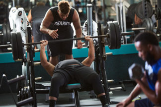 Male Gym-Goer Spotting Workout Partner On Bench Press In Gym