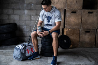 man at gym sitting on weights with Under Armor gym bag and water bottle