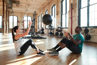 Man and Woman Working Out By Tossing Medicine Ball