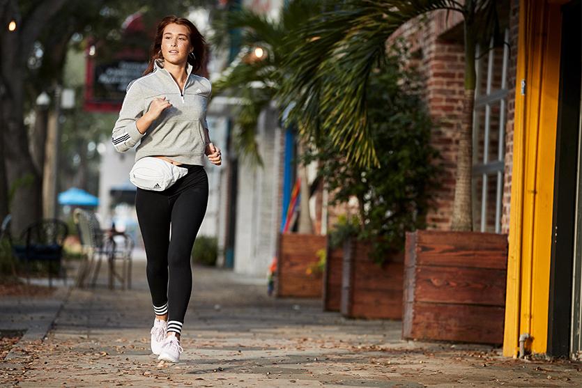 woman running at night wearing adidas fanny pack, adidas pullover, adidas joggers and adidas shoes