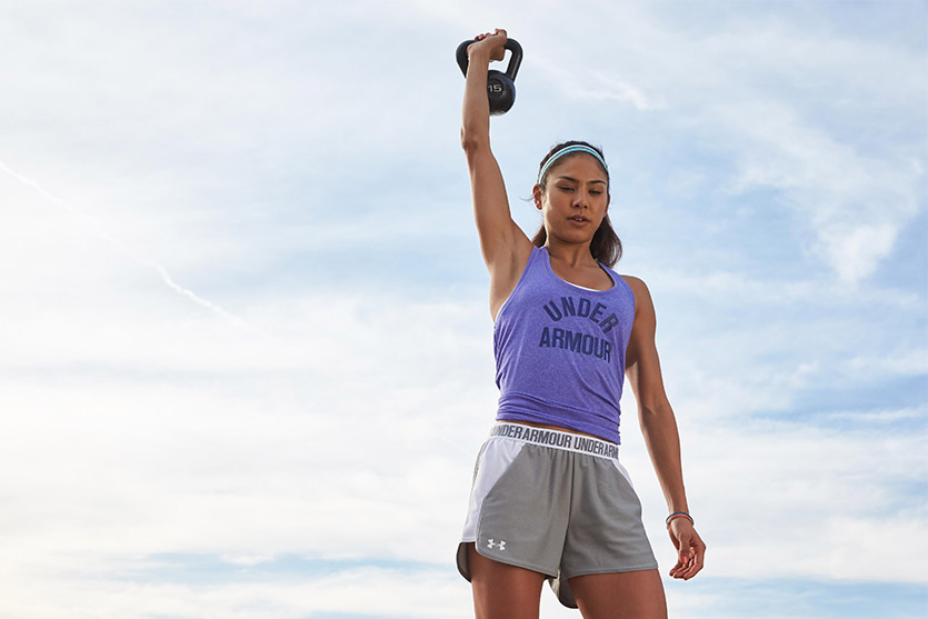 Woman Lifting Kettlebell Over Her Head