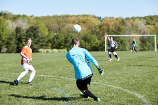 male soccer players playing on soccer field