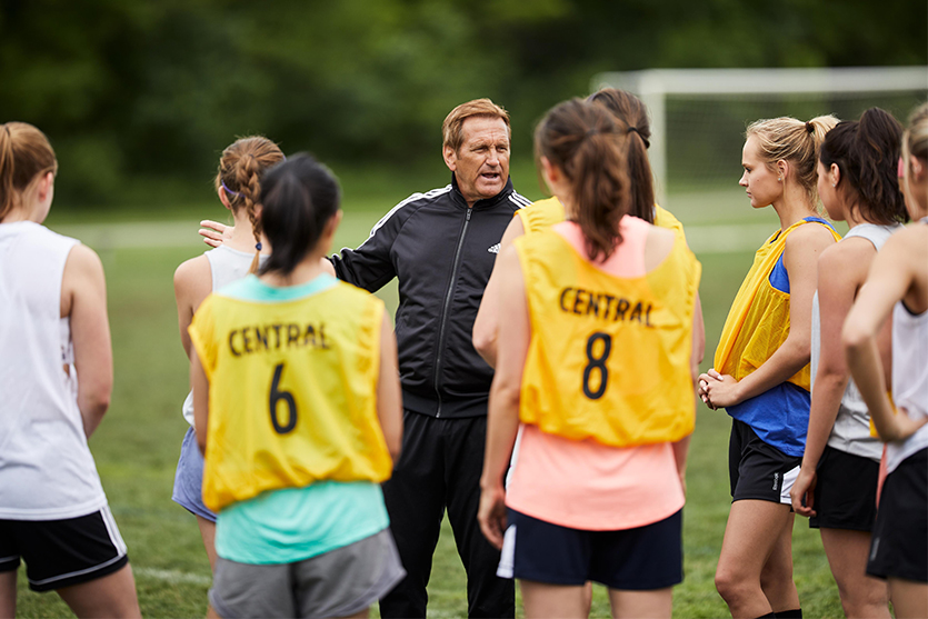 male soccer coach talking to female soccer players at practice or tryouts
