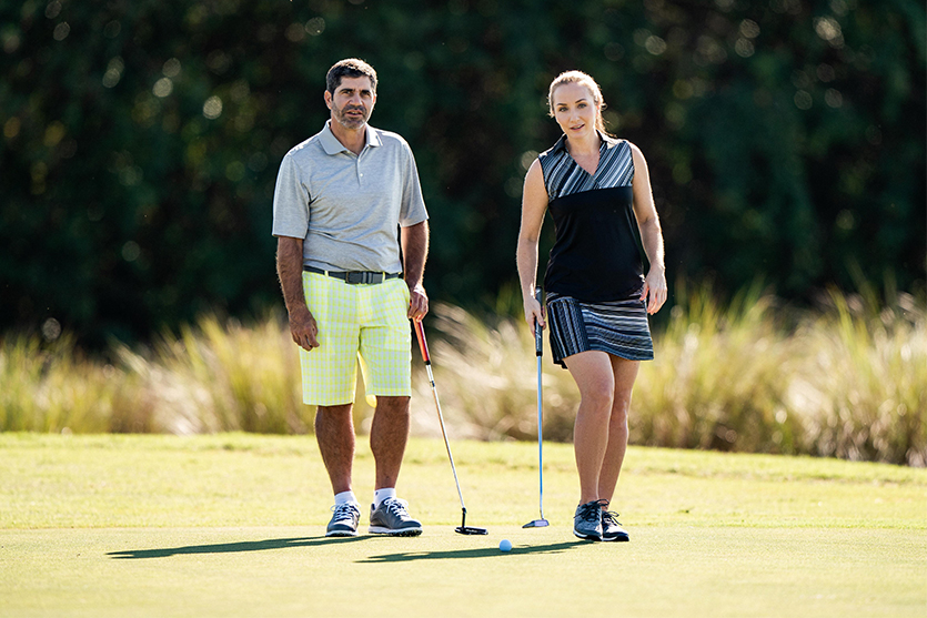 man and woman golfing on the putting green
