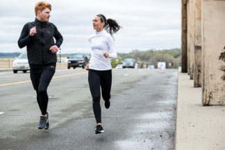 man and woman running on the road in the fall wearing running tights and long sleeves