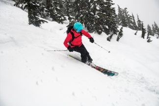 person skiing wearing red ski jacket and teal ski helmet