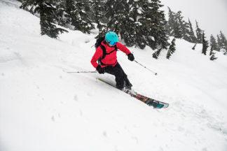 person skiing wearing red ski jacket and teal ski helmet