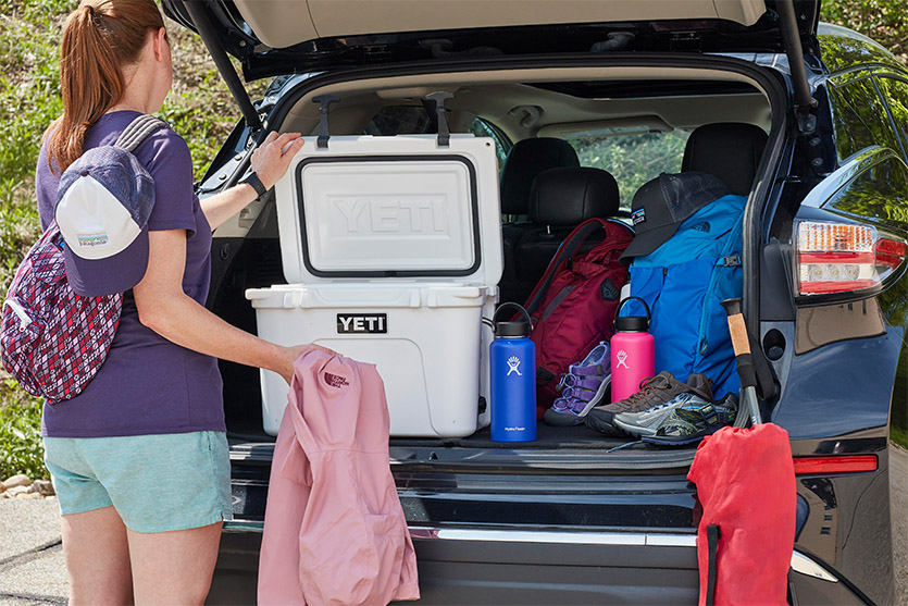 Woman Packing YETI Cooler In Trunk Of Car With Various Other Camping Gear