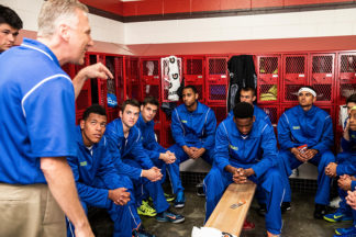 basketball coach motivating a team in the locker room before a basketball game