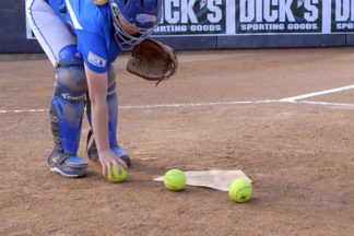 Softball Catcher Setting Up Softballs for Three-Ball Blocking Drill