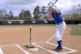 Softball Player Practicing Hitting With Batting Tee