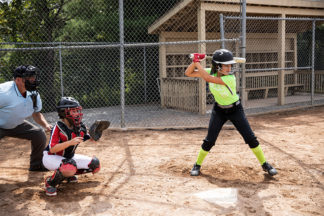 Softball Batter and Softball Catcher Preparing For Pitch as Umpire Watches On