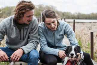 man and woman in Patagonia jackets with their dog