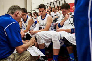 basketball coach looking over plays with his team during a timeout