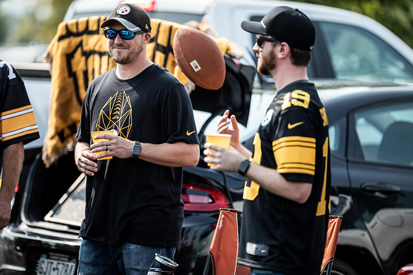 two guys at a Pittsburgh Steelers tailgate wearing Steelers gear