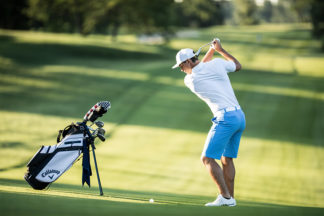 Male Golfer Swinging Club on Golf Course
