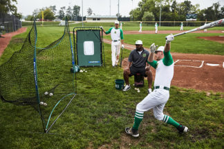 baseball players at practice hitting baseballs into nets