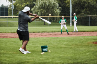 baseball coach at practice hitting baseball to his fielding players