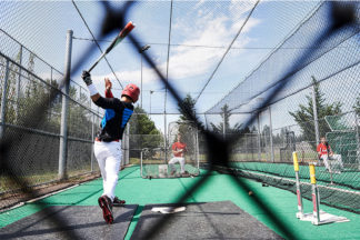 Baseball Player Practicing In Batting Cage