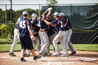baseball team celebrating a win at home plate