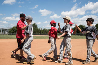 Baseball Coach And Players High-Fiving After A Game