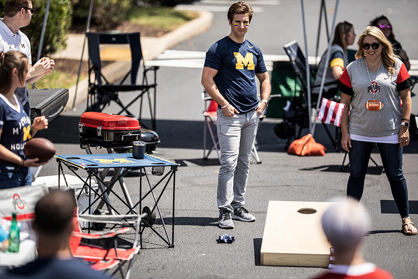 group of people at a tailgate playing corn hole