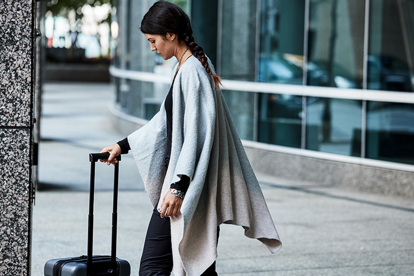 woman walking out of the airport with suitcase in hand