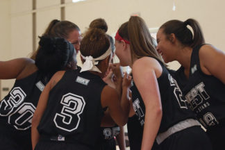 Female Basketball Players In Team Huddle