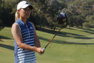 Danielle Kang holding a driver on a golf course wearing adidas golf apparel