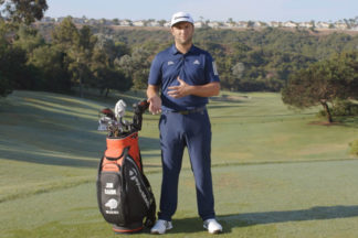 Jon Rahm wearing adidas golf apparel talking on a golf course with his golf bag