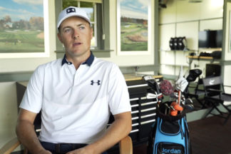 Jordan Spieth sitting down for an interview wearing Under Armor golf apparel