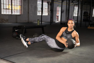 woman wearing nike fitness outfit doing Russian Twists with a medicine ball