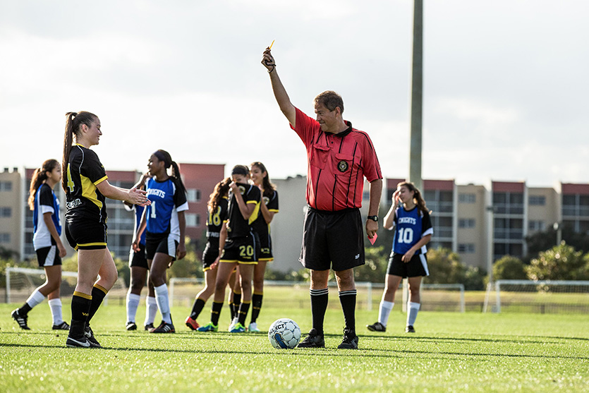 Soccer referee holding a yellow card during a girls soccer game