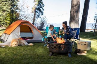 mom and daughter in their backyard camping with their golden retriever