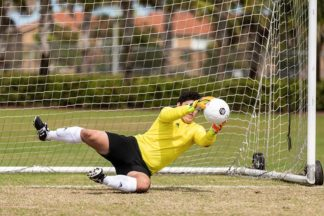 soccer goalkeeper dives to catch the soccer ball on the soccer field